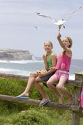 Two girls feeding chips to a seagull at the beach - stock photo