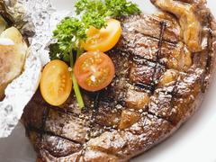 Grilled rump steak with tomatoes and baked potato Stock Photos