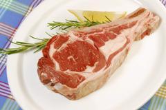 Raw lamb chop on a plate, rosemary, lemon Stock Photos