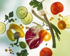 Vegetables, herbs, salad leaves & seasonings on a sheet of glass Stock Photos