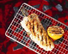 Monkfish on a barbecue with herbs and lemon - stock photo