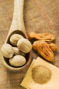 Nutmegs in wooden spoon, mace and ground nutmeg Stock Photos