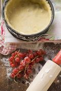 Baking tin lined with pastry, redcurrants and rolling pin Stock Photos