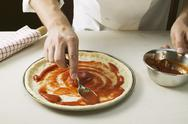 Stock Photo of Spreading pizza base with tomato sauce