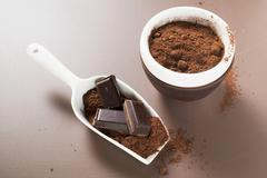 Pieces of chocolate and cocoa powder in scoop and bowl - stock photo