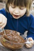 Child scraping remains of cake mixture out of glass bowl - stock photo