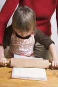 Mother and child rolling out puff pastry - stock photo