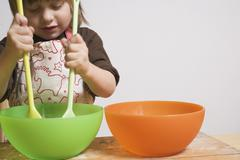 Child stirring bowl with two wooden spoons - stock photo