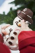 Child holding snowman biscuit - stock photo
