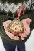 Child holding gingerbread Christmas tree (tree ornament) Stock Photos