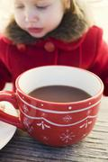Small girl behind large cup of cocoa - stock photo