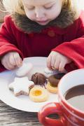 Small girl taking Christmas biscuit from plate - stock photo