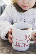 Small girl drinking large mug of cocoa Stock Photos