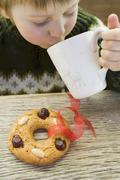 Stock Photo of Small boy drinking hot drink, gingerbread tree ornament