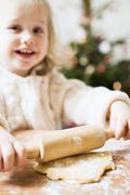 Small girl rolling out pastry (Christmas) - stock photo