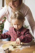 Mother and child cutting out Christmas biscuits Stock Photos