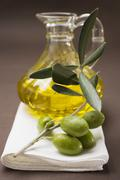 Olive sprig with green olives, carafe of olive oil behind Stock Photos