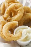 Deep-fried onion rings with mayonnaise - stock photo