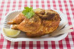 Stock Photo of Half a roast chicken in paper dish