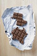 Bar of chocolate, partly eaten, on silver paper - stock photo