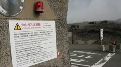 Red flashing light warns visitors of gas near the crater of a volcano in Japan Stock Footage