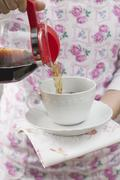 Woman pouring coffee into cup Stock Photos