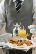 Butler serving breakfast tray with bacon, eggs & toast Stock Photos