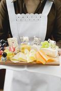 Waitress serving a cheese platter Stock Photos