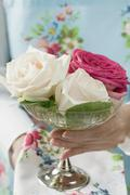 Woman holding a stemmed glass bowl with three roses - stock photo