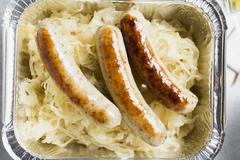 Sausages with sauerkraut in aluminium container to take away Stock Photos