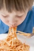 Small boy eating noodles with tomatoes Stock Photos