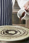 Pouring chocolate onto crêpe Stock Photos