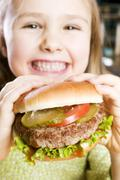 Girl holding large hamburger - stock photo