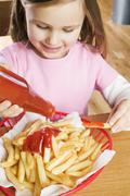 Girl putting ketchup on chips - stock photo