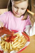 Stock Photo of Girl putting ketchup on chips