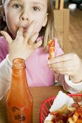 Stock Photo of Girl eating chips with ketchup