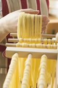 Hanging home-made ribbon pasta up to dry Stock Photos