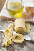 Home-made ribbon pasta, olive oil, eggshells Stock Photos