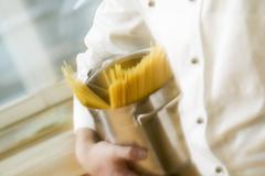 Chef hurrying through kitchen with spaghetti in pan Stock Photos