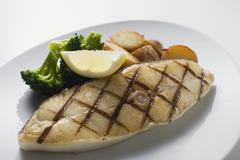 Grilled cod steak with potatoes and broccoli - stock photo