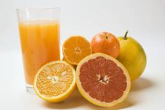 Glass of fruit juice and fresh citrus fruit Stock Photos