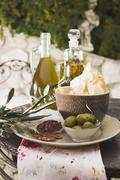 Olives, salami, crackers & olive oil on table out of doors - stock photo