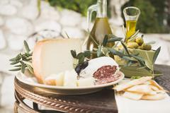 Cheese, salami, olives, olive oil, crackers on outdoor table Stock Photos