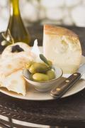 Cheese, green olives, crackers and olive oil on table Stock Photos
