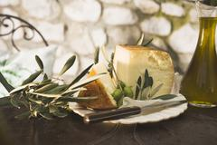 Cheese, green olives and olive oil on table out of doors - stock photo