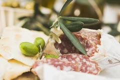 Salami, green olives and crackers Stock Photos
