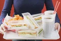 Woman holding sandwiches, cola and crisps on tray Stock Photos