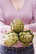 Woman holding three artichokes - stock photo