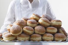 Waitress holding tray piled high with doughnuts - stock photo