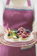 Woman in apron holding assorted berry tarts - stock photo